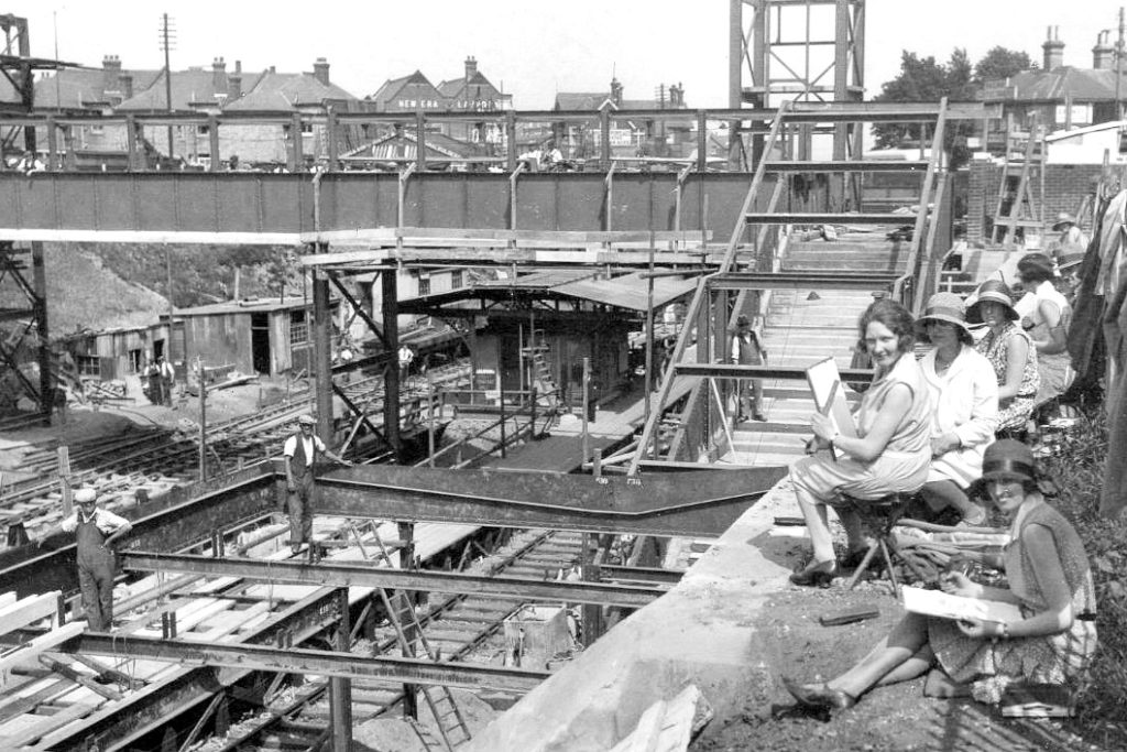 black and white photo of construction work at Pokesdown Station about 1930. New Era laundry can be seen in the background. Workmen and a group of women observing or drawing the scene are in the photo.