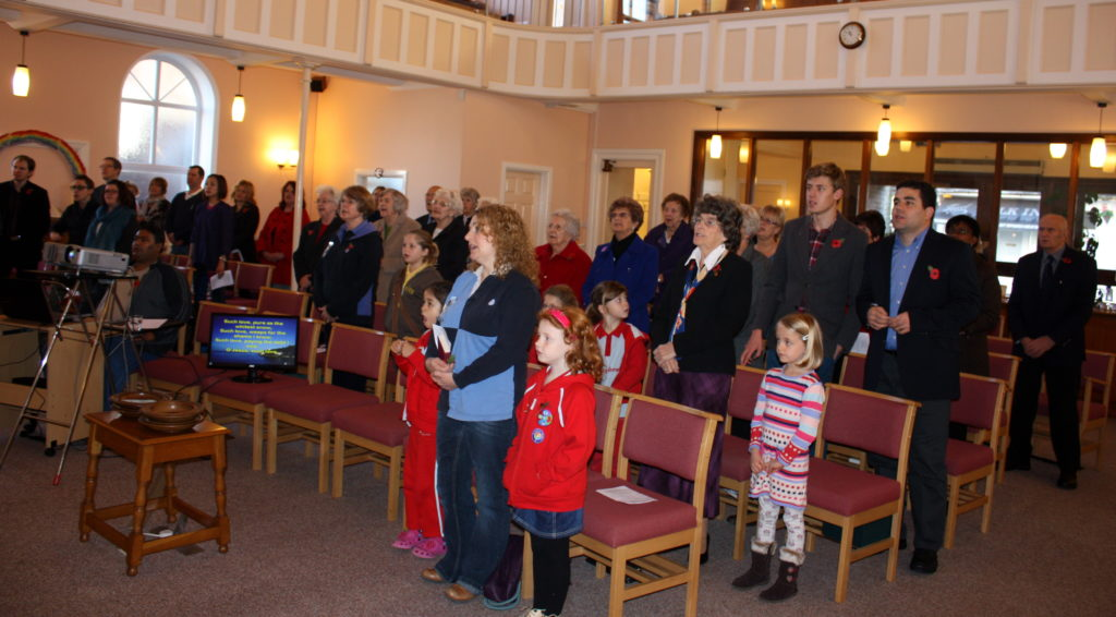 colour photo of people stood singing in church